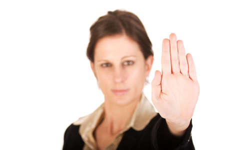 motioning: Brunette business woman holding hand up, looking annoyed. Hand in focus, face out of focus.