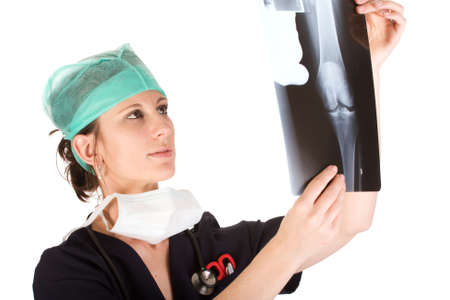 Young attractive Caucausian female health care worker examining an x-ray of a human knee. Isolated on white background photo