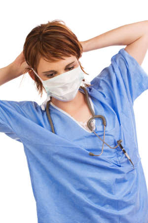medical assistant: Young adult Caucasian female medical assistant dressed in scrubs putting on a protective mask Stock Photo