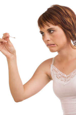 Young female Caucasian adult measuring her body temperature using a fever pen and looking worried photo