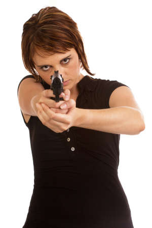 herself: Young woman defending herself with a pistol. Face in focus, pistol out of focus