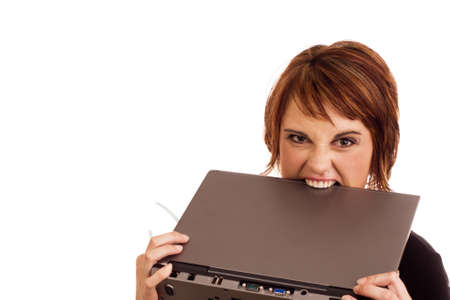 Frustrated Caucasian business woman holding her glasses and biting laptop in anger photo