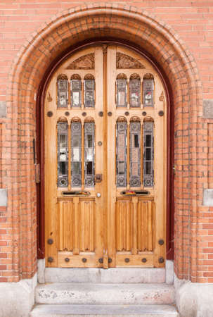 Closed antique wooden and glass door in red brick building photo