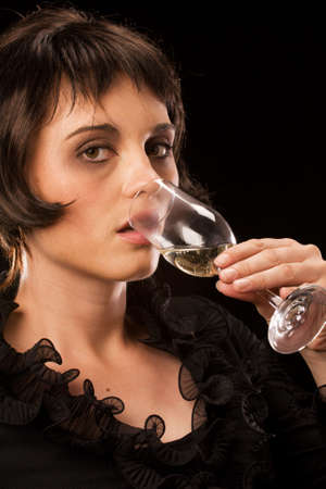 Young attractive caucasian female drinking sparkling wine out of a champagne flute photo