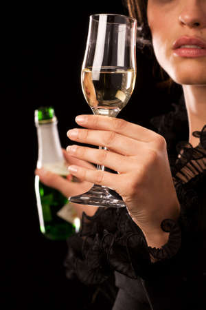 Young caucasian woman holding a champagne bottle and glass photo
