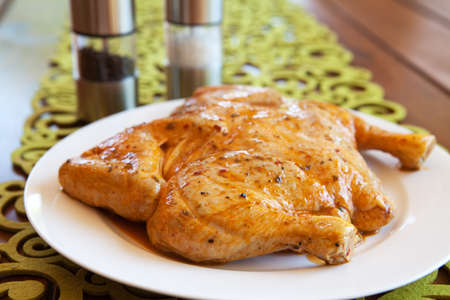 Uncooked whole marinated chicken on a white plate