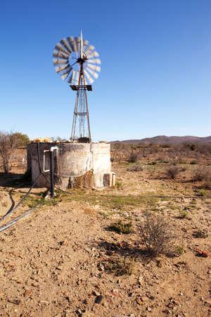 blown: Wind blown windpump pumping water next to dam in Karoo Stock Photo
