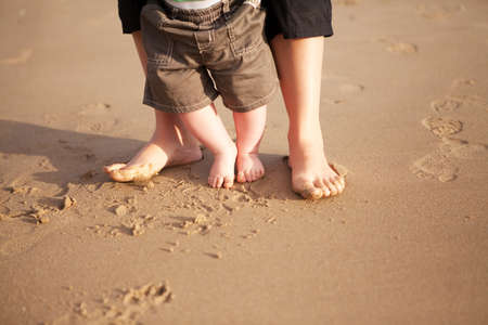 Mother and baby walking on beach sand photo