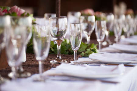 Wedding decor, wine glasses and champagne flutes on table. Selective focus photo