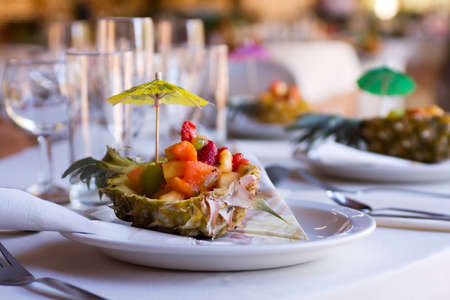 Fruit salad appetizer served in half pineapple at wedding reception photo