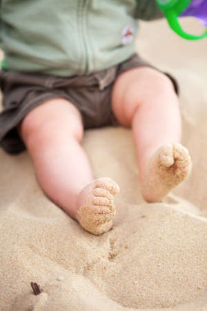 feet in sand: Curly toed baby feet covered with beach sand Stock Photo