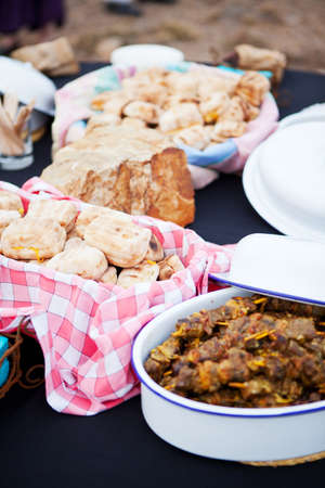 south african: Roasted bread and mutton kebabs in dishes on a table
