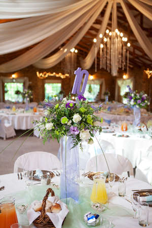 venue: Laid table with flower bouquet and decorations at wedding reception