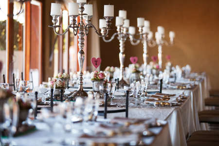 Beautifully decorated tables with candelabra at wedding reception, selective focus photo
