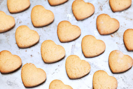 Home made heart shaped shortbread cookies on baking tray photo