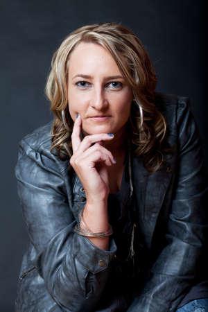 faux: Una giovane donna attraente che indossa una giacca di ecopelle grigio