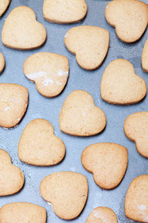Rows of heart shaped shortbread biscuits on metal baking tray photo
