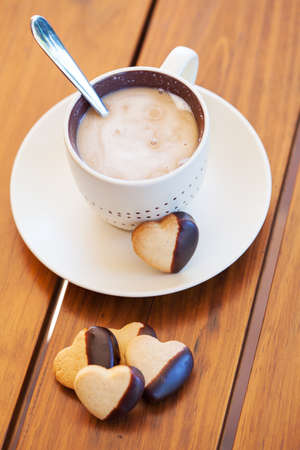Cup of coffee served with chocolate-dipped heart shaped biscuits photo