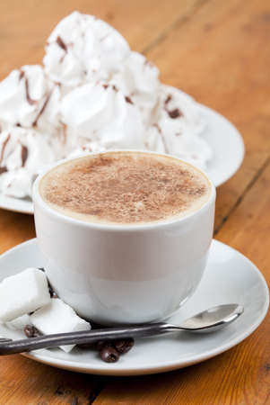 Cup of cappuccino with foam and meringues on white plate photo