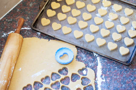 baking tray: Heart shaped cookies in the making next to a wooden rolling pin, raw dough and heart shaped cookie cutter