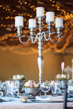 Wedding reception hall with decorated tables, selective focus with blurred fairy lights in background photo