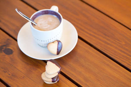 Stacked heart shaped cookies and cup of coffee on wooden table, copyspace photo