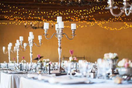 recepcion: Wedding hall de recepci�n, con una decoraci�n incluyendo velas, cubiertos y vajilla, el enfoque selectivo en candelabros Foto de archivo