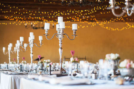 wedding reception: Wedding reception hall with decor including candles, cutlery and crockery; selective focus on candelabra