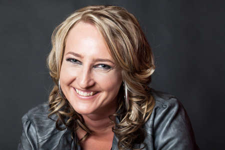 Close-up of happy smiling young blonde lady wearing fake leather jacket photo