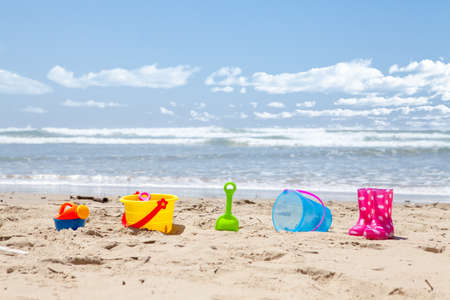 brightly colored: Brightly colored plastic beach toys on the beach with the ocean and clouds in background Stock Photo