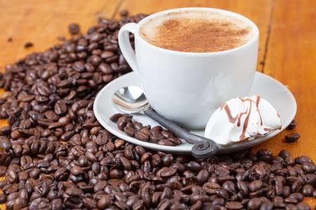 Freshly brewed cup of coffee served with meringue between coffee beans photo