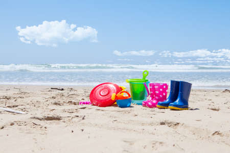 spades: Brightly colored plastic toys and gumboots on the beach sand