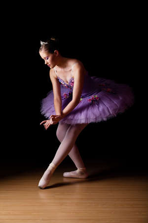 Beautiful young Caucasian female ballet dancer wearing lilac tutu against black backdrop in studio photo