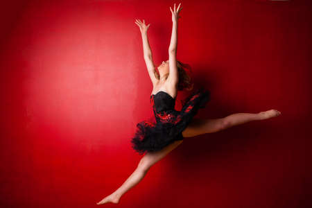 air jump: Young Caucasian ballerina executing a jump against bright red wall, throwing her hands in the air