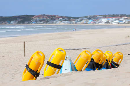 flotation: Beach with colorful lifesaving flotation devices, sea and town in background