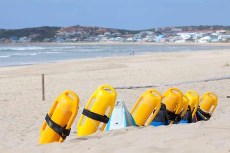 salvavidas: Playa con dispositivos de flotación para salvar vidas colorido, el mar y la ciudad en segundo plano