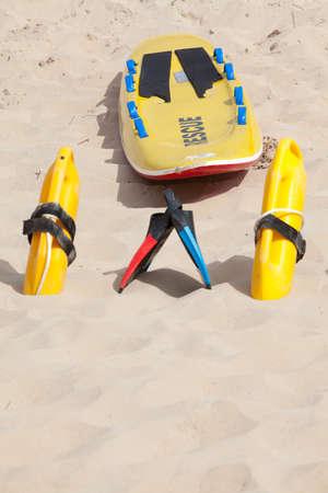 lifesaving: Lifesaving raft, floatation devices and swimming fins on beach Stock Photo