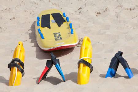 lifesaving: Colorful lifesaving equipment lying on the beach sand in the hot summer sun Stock Photo