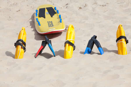 flotation: Bright yellow flotation devices and rescue equipment on the beach