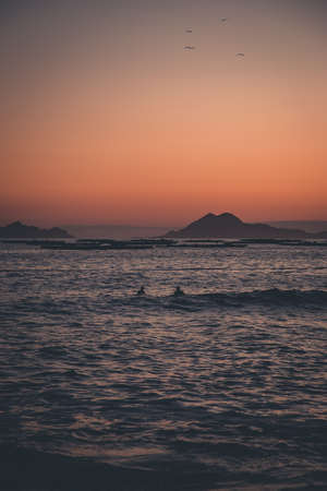 Two surfers in the sea in front of the islands during a sunset