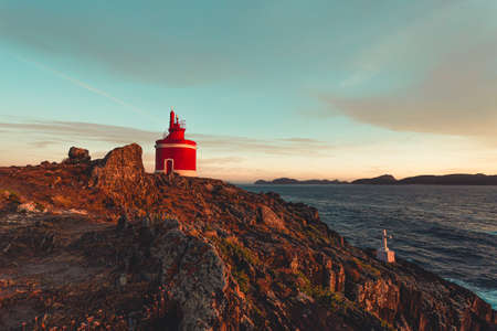 Horizontal shot of the red lighthouse during the sunset