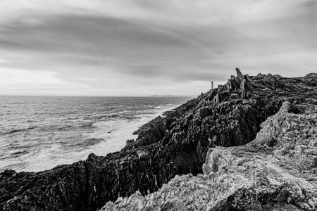 Black and white dramatic shot of the lighthouse on the broken coast of Galicia