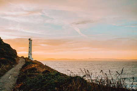 Horizontal shot of the white lighthouse during the sunset Stock fotó