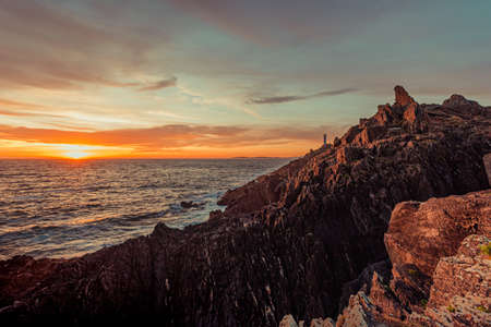 Dramatic horizontal shot of a white lighthouse during the sunset from the rocks of the coast Stock fotó
