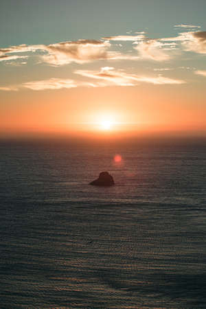 Massive sunset with sun flares over the ocean with a rock in the middle of the sea Stock fotó