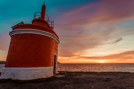 Colorful sky during the sunset near a red lighthouse