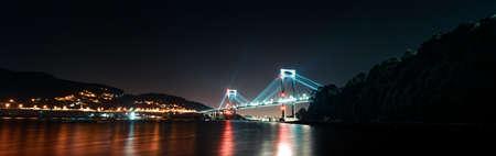 Super panoramic view of a full of lights bridge during night Stock fotó