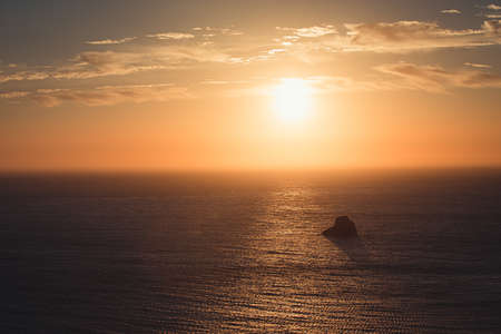 Massive sunset over the ocean with a rock in it Stock fotó