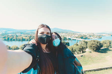 Two young girls taking a selfie with the masks on during a sunny day