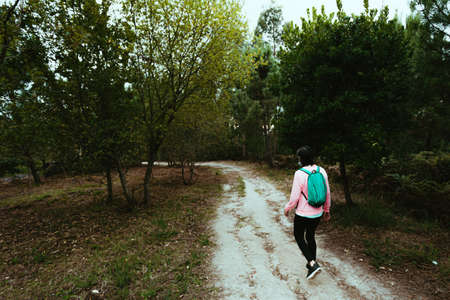 An old woman from behind walking in the forest doing trekking